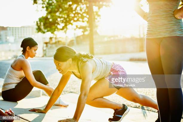 Woman stretching with friends before morning run