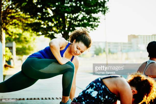Woman stretching with friends before run