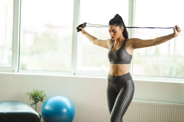Mujer utiliza la comba, uno de los materiales para hacer ejercicio en casa