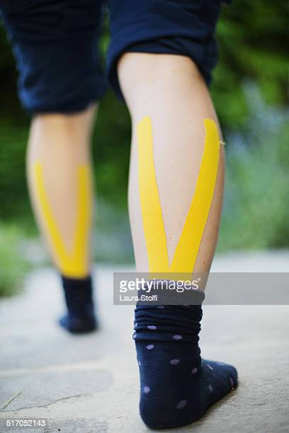 Woman stretching with kinesiotape on her calfs
