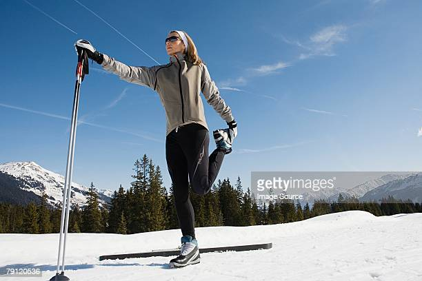 Woman stretching with ski poles