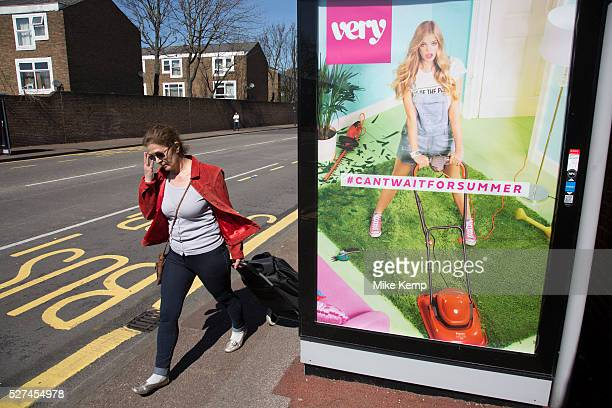 Woman striding past a bus shelter advert for retail clothes shop Very Newham East London UK The advertisement depicts a young girl wearing dungarees...