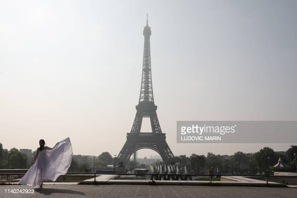 A woman strikes poses for a photographer close to the Trocadero Fountains overlooking the Tour Eiffel in Paris on April 30 2019