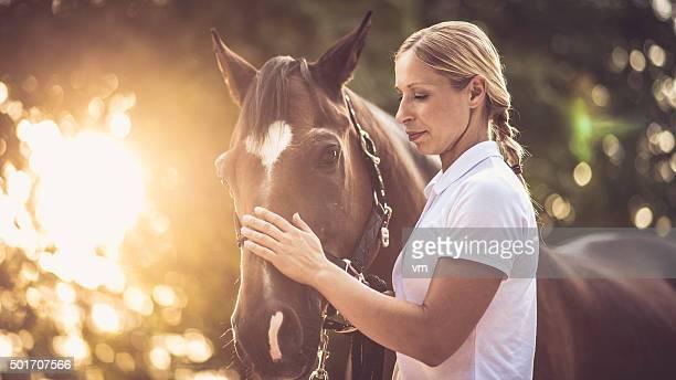 mujer acariciar el caballo marrón de la cabeza - 1 woman 1 horse fotografías e imágenes de stock