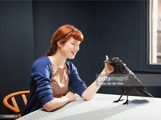 Woman stroking crow standing on table.