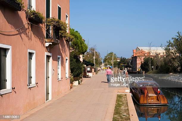 Woman strolling along canal.
