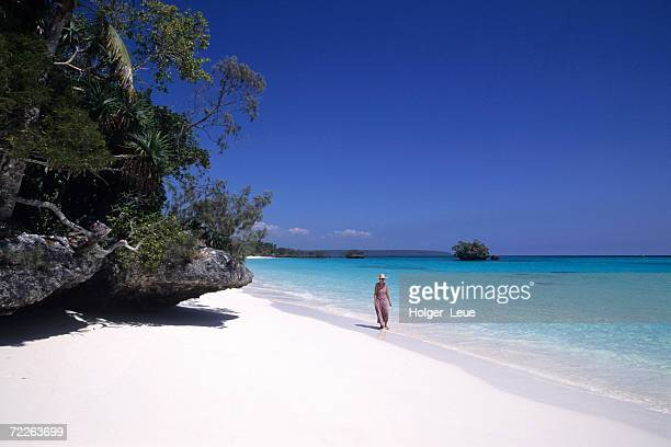 Woman strolling along Luengoni Beach, New Caledonia
