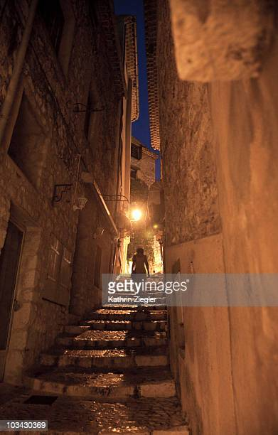 woman strolling through old town at night