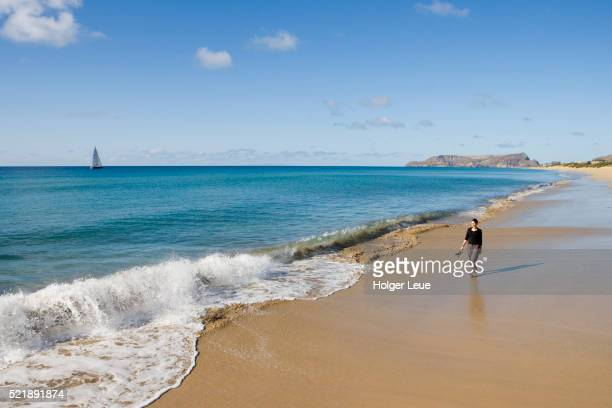 Woman strolls along golden sand of Porto Santo Beach as wave breaks, Porto Santo, near Madeira, Portugal