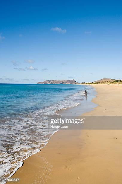Woman strolls along Porto Santo Beach