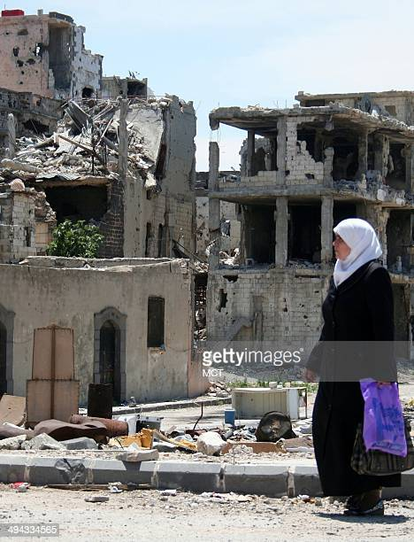 A woman strolls out of the ruins of the Old City of Homs which was devastated by a Syrian army siege that ended in a truce and a May 79 withdrawal by...
