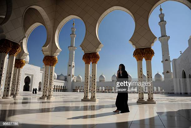 A woman strolls the Sheikh Zayed Mosque on December 19 2009 in Abu Dhabi United Arab Emirates The Mosque named after Sheikh Zayed bin Sultan Al...