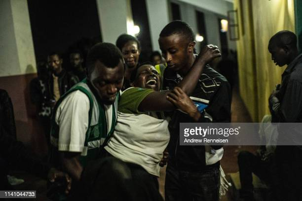 Woman struck with grief is carried out of a candlelight commemoration ceremony of the 1994 genocide on April 07, 2019 at Amahoro Stadium in Kigali,...