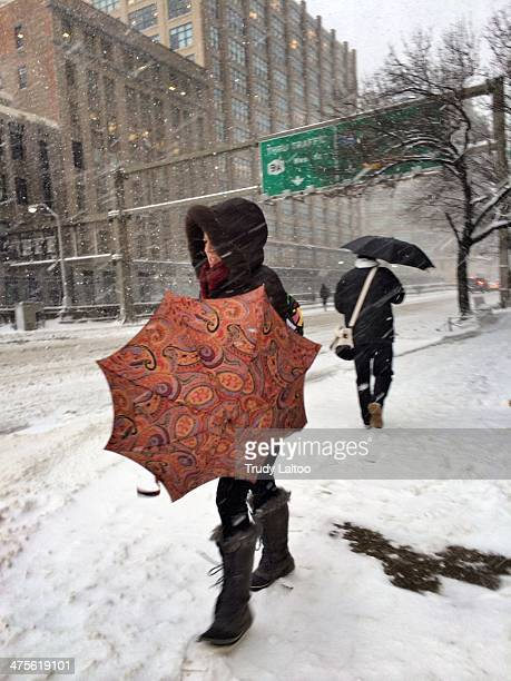 Woman struggle with an umbrella after exiting the Canal Street Station on February 13, 2014 in New York City.
