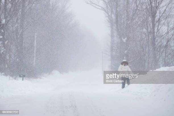 A woman struggles down a rural road as snow in Northeast Pennsylvania reached two feet and still falling on March 14 2017 in New Milford Pennsylvania...
