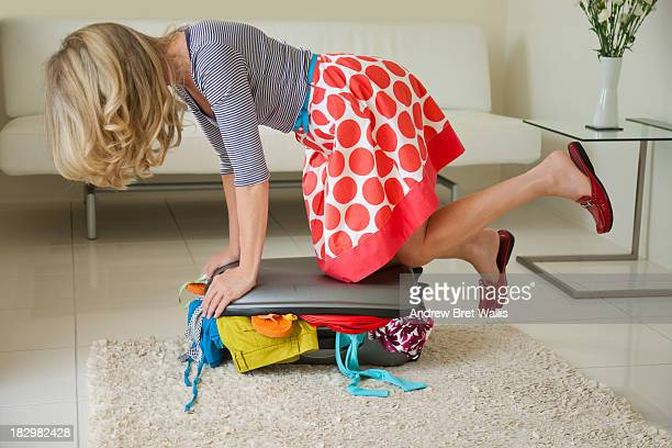 Woman struggles to close suitcase full of clothes