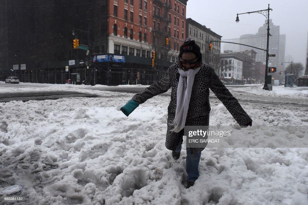 TOPSHOT - A woman struggles to cross a snow covered street in New York city on March 14, 2017. Winter Storm Stella dumped sleet and snow across the northeastern United States on Tuesday but spared New York from the worst after authorities cancelled thousands of flights and shut schools. Blizzard warnings were in effect in parts of Connecticut, Massachusetts and upstate New York, but were lifted for New York City, the US financial capital home to 8.4 million residents, where snow turned to sleet, hail and rain. BARADAT