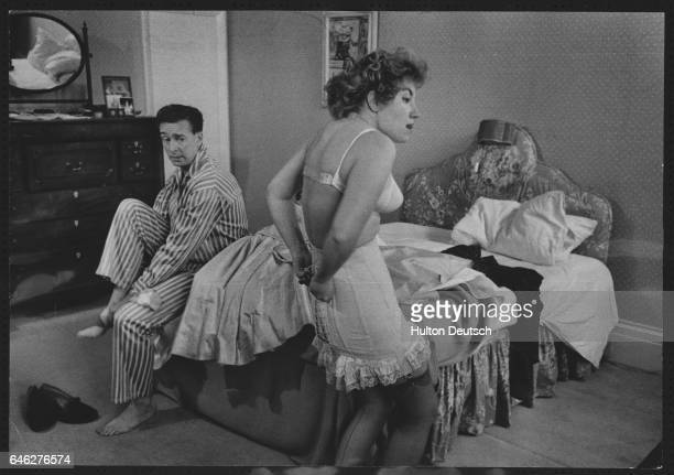A woman struggles to do up her corset as a couple getting dressed in their bedroom