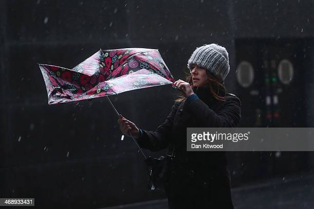 A woman struggles to keep dry in the rain under her umbrella at Southwark Crown Court on February 12 2014 in London United Kingdom The Environment...