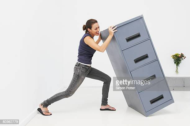 woman struggles with filing cabinet - picking up stock pictures, royalty-free photos & images