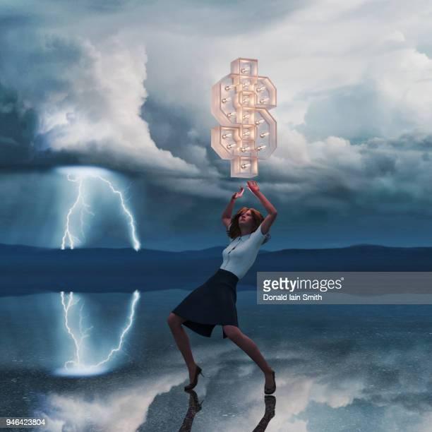 Woman struggling beneath glowing dollar sign in stormy landscape