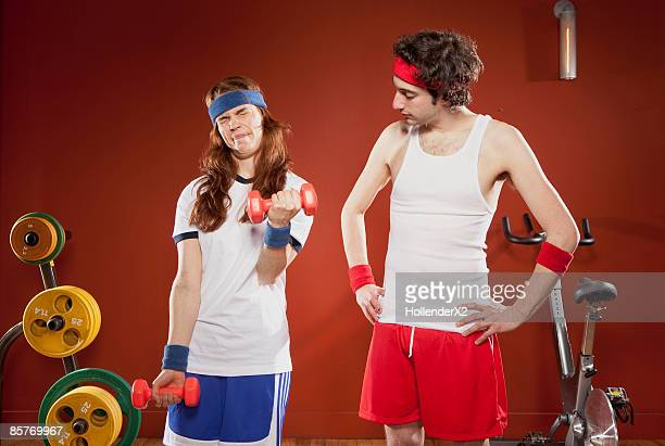 woman struggling to lift small weight with man