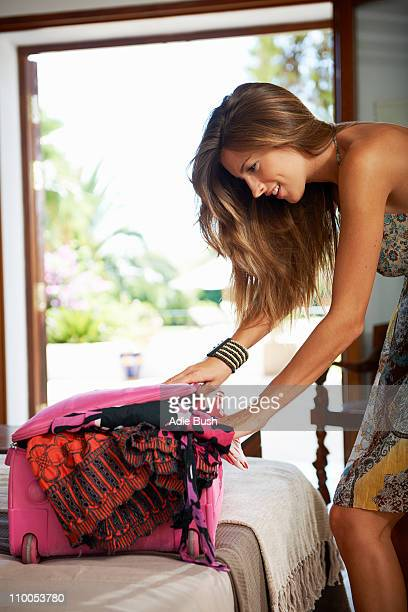 Woman struggling to pack suitcase