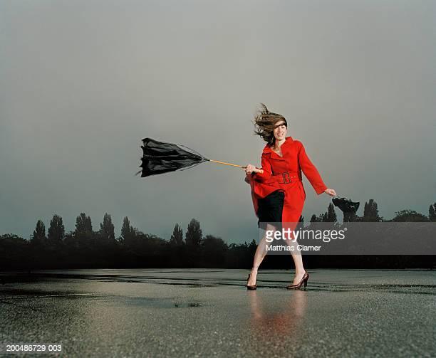 Woman struggling with broken umbrella in wind and rain