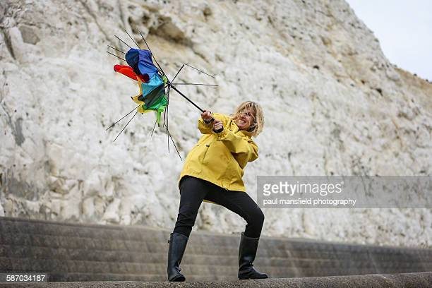 Woman struggling with broken umbrella