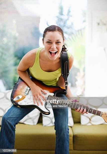 Woman strumming guitar