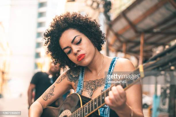 woman strumming on guitar outdoors - modern rock stock pictures, royalty-free photos & images
