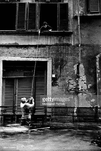 A woman stuck for the flood receiving a basket of food Florence November 1966