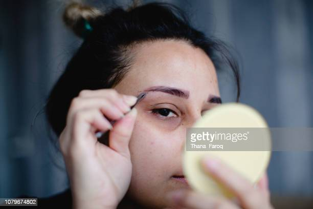 A woman looking at mirror and tweezing her eyebrows