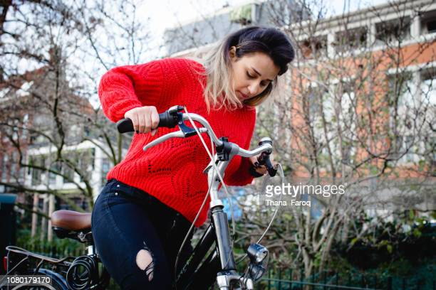 a woman learning how to ride on bike outside - la haye photos et images de collection