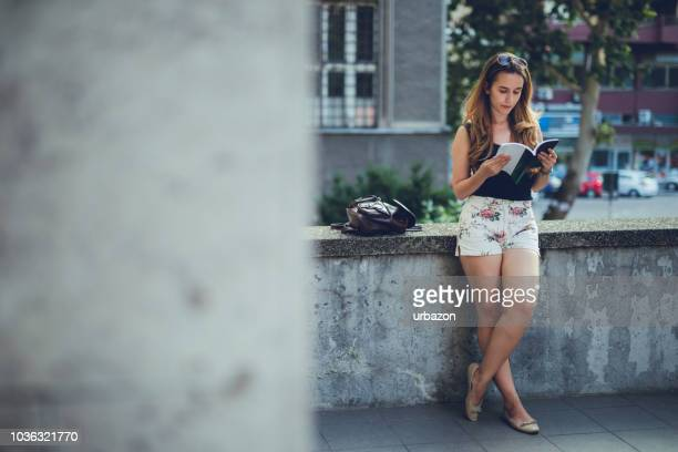 woman student reading book downtown - legs crossed at ankle stock pictures, royalty-free photos & images