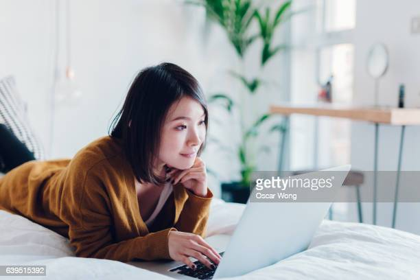 woman student using laptop in bedroom - surfing the net stock pictures, royalty-free photos & images