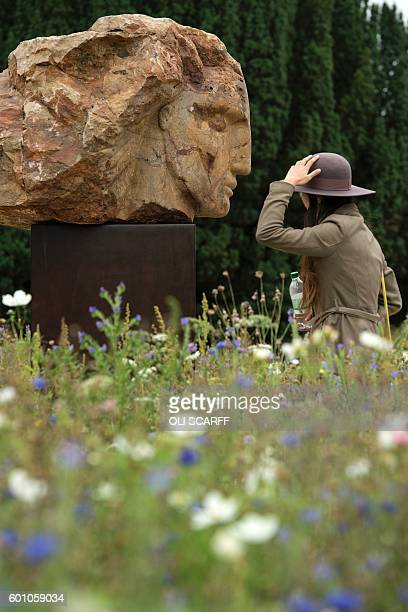A woman studies a sculpture by British artist Emily Young entitled 'Red Mountain Head' that features in the 'Beyond Limits' exhibition in the grounds...