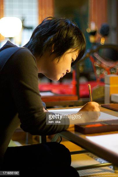 A woman studies jananese calligraphy