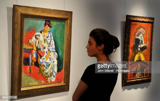A woman studies the Andre Derain painting of Madame Matisse au Kimono painted in 1905 with a painting by Picasso titled Buste d'homme a la pipe The...