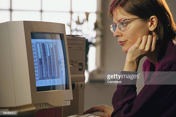 Woman studying bar graph on computer