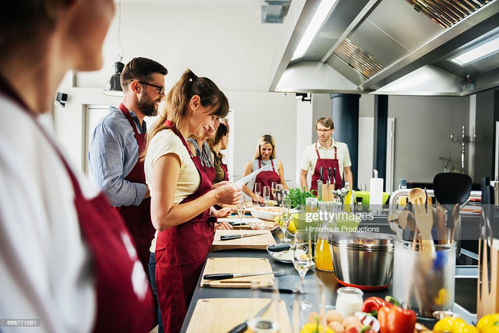 Woman studying recipe in cooking class : Stock Photo