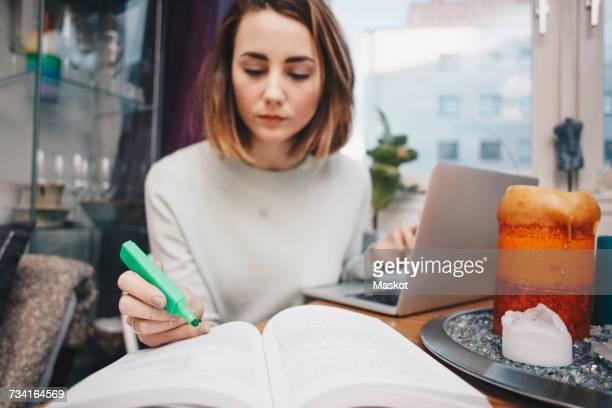 woman studying with laptop and book at table in college dorm - vuxen bildbanksfoton och bilder