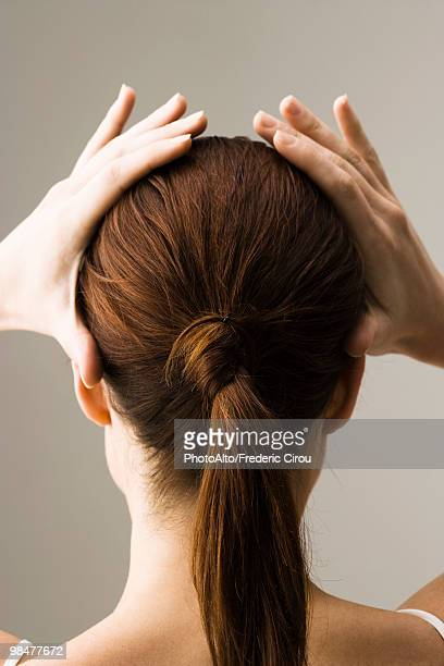 woman styling hair, rear view - ponytail stock pictures, royalty-free photos & images