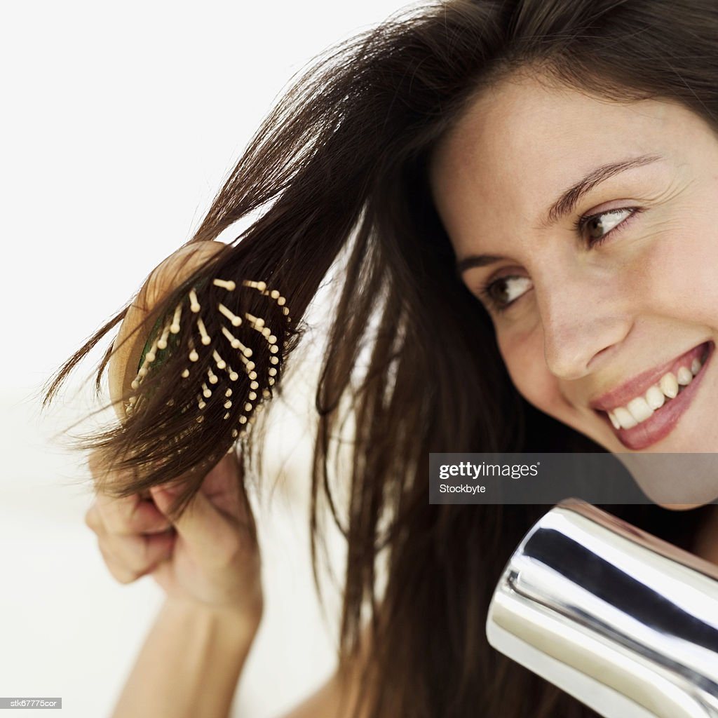 woman styling hair with blow dryer and brush : Stock Photo