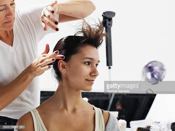 Woman styling model's (15-17) hair backstage at fashion show