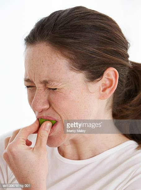 Woman sucking on lime quarter, close up