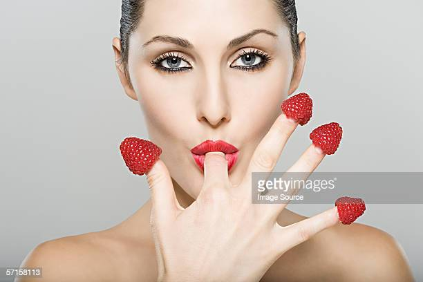 Woman sucking strawberry off her finger