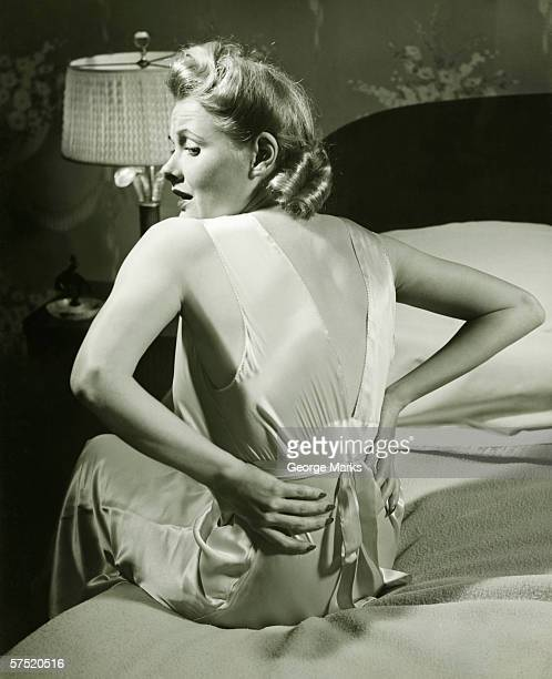 Woman suffering backache sitting on bed, (B&W)