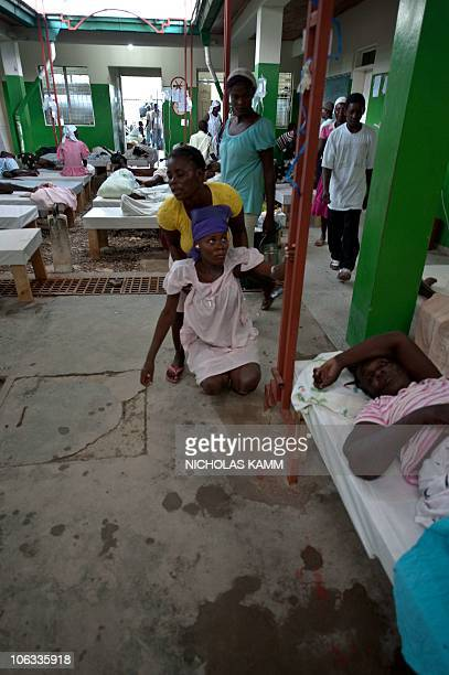 A woman suffering from cholera unable to stand is helped up by a relative at the Charles Colimon hospital in Petite Riviere on the Artibonite river...
