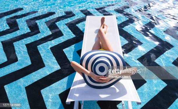 woman summer fashion. long legs. healthy skin in bikini. sun hat. sunglasses sunbathing by swimming pool on travel holidays vacation. beauty. wellness. lifestyle - swimming pool stock pictures, royalty-free photos & images